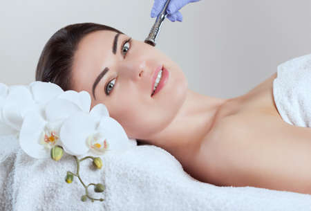 Photo pour The cosmetologist makes  Microdermabrasion procedure of the facial skin of a beautiful, young woman in a beauty salon.Cosmetology and professional skin care. - image libre de droit