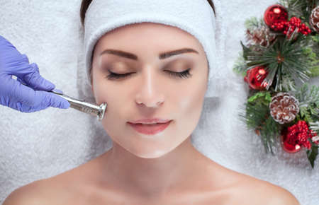 Photo pour The cosmetologist is doing the procedure of cleaning facial skin of a beautiful, young woman - image libre de droit