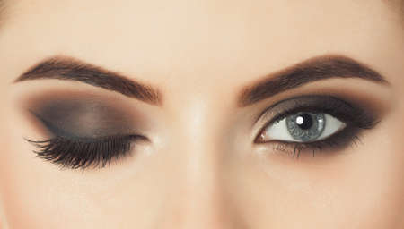 Photo for Beautiful woman with long eyelashes and with beautiful evening make-up. Eyes close up.One eye is closed and the other is open. - Royalty Free Image