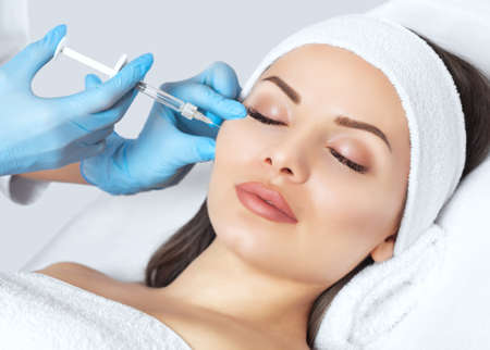 Foto de The doctor cosmetologist makes the Rejuvenating facial injections procedure for tightening and smoothing wrinkles on the face skin of a beautiful, young woman in a beauty salon.Cosmetology skin care. - Imagen libre de derechos