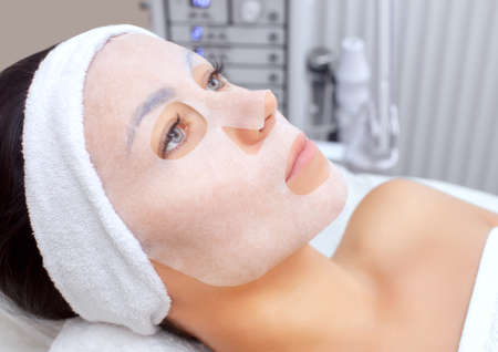 Photo pour The cosmetologist for procedure of cleansing and moisturizing the skin, applying a sheet mask to the face.Cosmetology and professional skin care. - image libre de droit