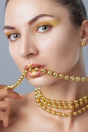 Photo pour Portrait of a beautiful happy woman with beautiful creative makeup in gold colors. She has gold beads on her neck, in her hands and on her lips, and gold earrings. Make-up concept. - image libre de droit