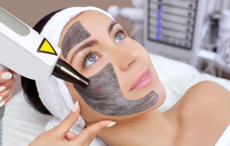 Foto de Cosmetologist does Carbon face peeling procedure of a beautiful, young woman in a beauty salon. Hardware cosmetology treatment and Spa. - Imagen libre de derechos
