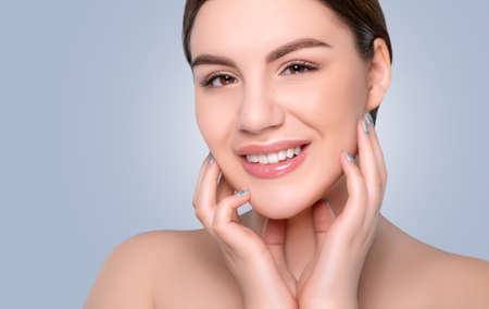 Photo pour Portrait of a beautiful happy girl with a beautiful smile, clean and healthy skin and nude makeup on a blue background. Cosmetology skin care and makeup. - image libre de droit
