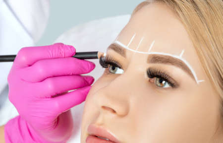 Photo pour Woman Having Permanent Make-up Tattoo on her Eyebrows.Permanent make-up for eyebrows in beauty salon. Closeup beautician doing tattooing eyebrow. Professional makeup and cosmetology skin care. - image libre de droit