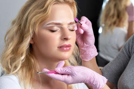 Photo for Blonde woman having permanent make-up tattoo on her eyebrows. Closeup beautician doing tattooing eyebrow.Professional makeup and cosmetology skin care. - Royalty Free Image