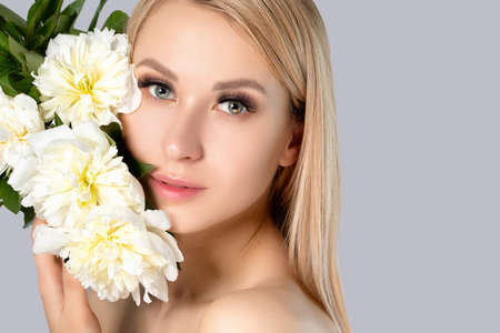 Photo pour Portrait of a beautiful blonde woman with long hair, beautiful fresh makeup and healthy clean skin with peonies in her hands. Makeup and cosmetology concept. - image libre de droit