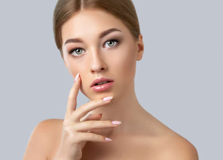 Photo pour Beautiful young blonde with naked shoulders, with clean fresh skin, pink manicure and beautiful makeup, plump lips. Make-up concept, Aesthetic cosmetology and hair care. Problem skin treatment. - image libre de droit