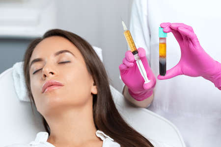 Photo pour Beautician will do PRP therapy for the face against wrinkles. She has blood plasma for injections and a syringe with plasma in her test tube. Cosmetology in the beauty salon. - image libre de droit