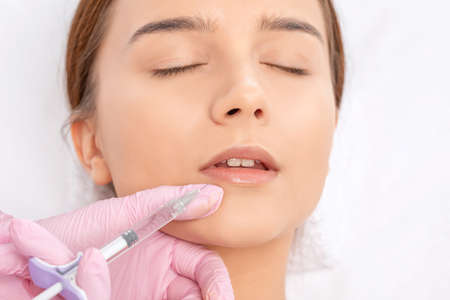 Photo pour Cosmetologist does injections for lips augmentation and anti wrinkle in the nasolabial folds of a beautiful woman. Women's cosmetology in the beauty salon. - image libre de droit