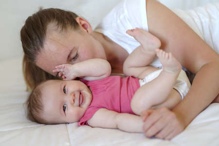 Photo pour Mother bonding with his baby girl, while both resting on the bed - image libre de droit