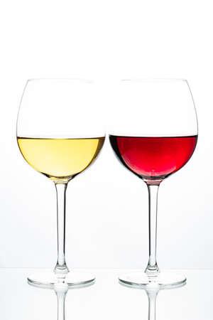 Foto de Two glasses with wine on a white background. Red wine. White wine. Apple juice. Cherry juice. - Imagen libre de derechos