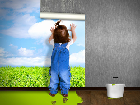 Funny child hanging wallpaper, doing repairs. Eco house concept.