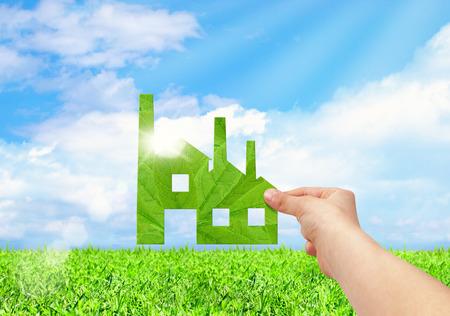 Foto de Hand hold factory iconon field and blue sky background, Eco green factory concept - Imagen libre de derechos