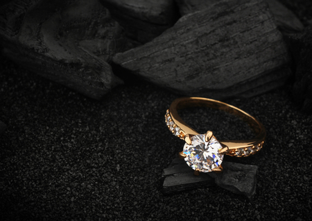 Photo pour jewelry ring witht big diamond on dark coal and black sand background - image libre de droit