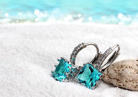 Photo pour Jewelry earrings with aquamarine on sand beach background, soft focus - image libre de droit