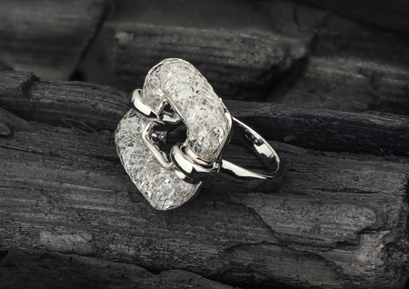 Photo pour Golden Jewelry ring with diamonds, on black coal as background - image libre de droit