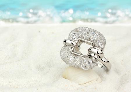 Photo pour Jewelry ring on sand beach as background - image libre de droit