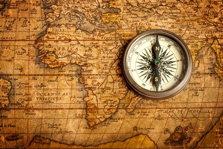 Old vintage retro compass on ancient map