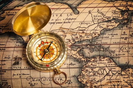 Old vintage retro golden compass on ancient map