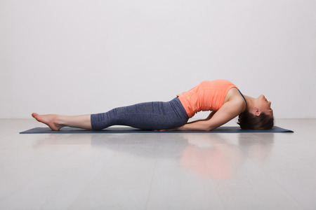Beautiful sporty fit yogini woman practices yoga asana Matsyasana - fish pose variation in studio