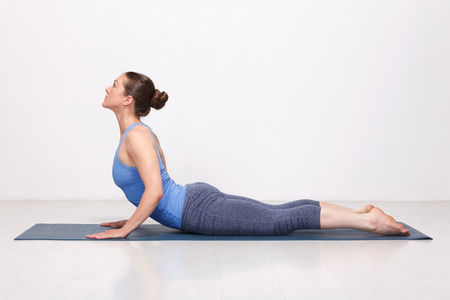 Beautiful sporty fit yogini woman practices yoga asana bhujangasana - cobra pose in studio