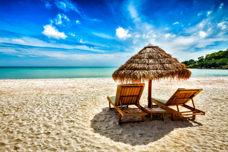 Photo pour Vacation holidays background wallpaper - two beach lounge chairs under tent on beach. Sihanoukville, Cambodia - image libre de droit