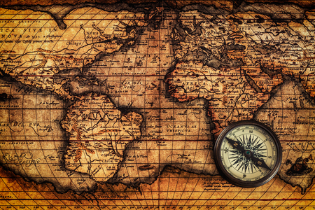 Travel geography navigation concept background - old vintage retro compass on ancient world map