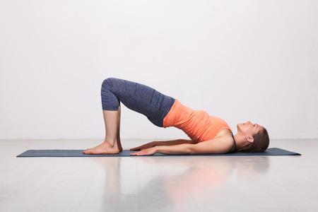 Beautiful sporty fit yogini woman practices yoga asana setu bandhasana - bridge pose beginner variation in studio