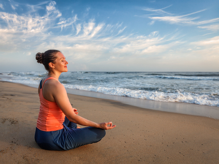 Foto de Young sporty fit woman doing yoga - meditating and relaxing in Padmasana Lotus Pose) with chin mudra outdoors at tropical beach on sunset - Imagen libre de derechos