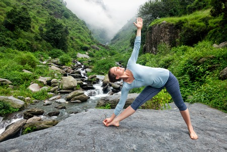 Foto de Woman doing Ashtanga Vinyasa yoga asana Utthita trikonasana - extended triangle pose outdoors at waterfall in Himalayas - Imagen libre de derechos
