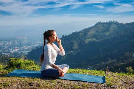 Photo pour Woman practices pranayama yoga breath control in lotus pose padmasana outdoors in Himalayas in the morning on sunrise. Himachal Pradesh, India - image libre de droit