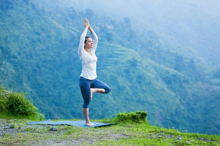 Woman practices balance yoga asana Vrikshasana tree pose in Himalayas mountains outdoors. Himachal Pradesh, India. Panorama