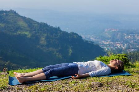 Photo pour Woman relaxes in yoga asana Savasana - corpse pose outdoors in Himalayas. Himachal Pradesh, India - image libre de droit