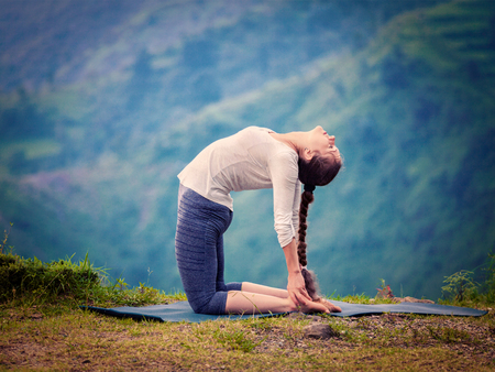 Photo pour Yoga - outdoors  young beautiful slender woman yoga instructor doing camel pose Ustrasana asana exercise outdoors. Vintage retro effect filtered hipster style image. - image libre de droit