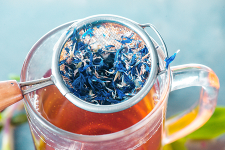 Cornflower welding close-up in a tea strainer on a glass cup.