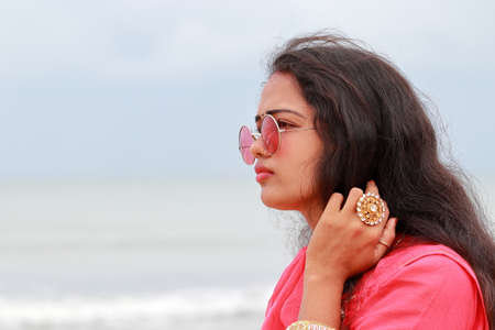 Photo pour A portrait head shot of a beautiful young Indian woman standing alone on the shores of Chennai,And gorgeous lady models looking away and wearing their culture clothes, sunglasses and cosmetic apparel - image libre de droit
