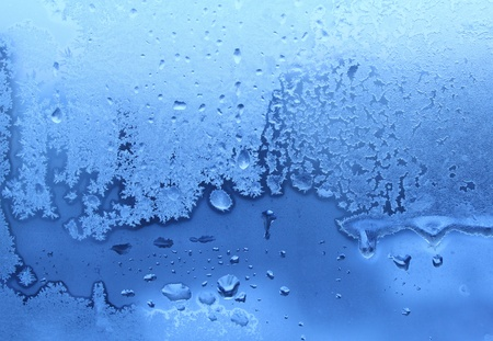 blue ice and water drops on winter glass
