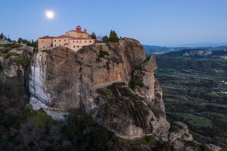 Meteora cliffs and the Holy Monastery of St  Stephen  founded in the middle of 16th century AD  in Greece under full moon