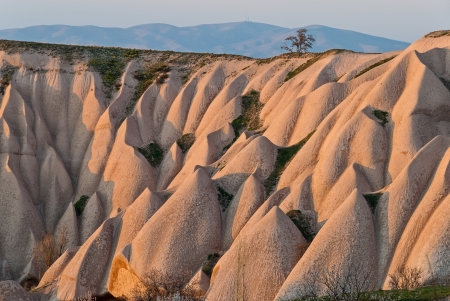 Typical landscape with sandstone formations in Cappadocia, Turkey, at sunset