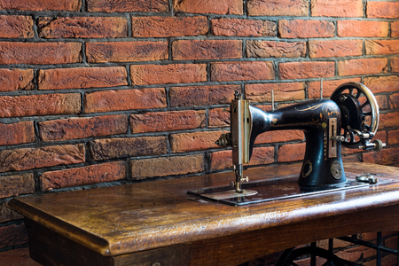 Photo for Old sewing machine with its wooden table near a wall of red bricks in Greece - Royalty Free Image