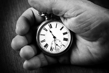 Pocket watch in senior man's hand