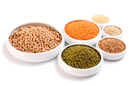 Millet, barley, buckwheat grains, red lentil, green soybeans and chick peas in ceramic bowls, isolated on white