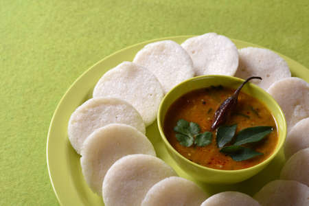 Photo pour Idli with Sambar in bowl on green background, Indian Dish : south Indian favourite food rava idli or semolina idly or rava idly, served with sambar and green coconut chutney. - image libre de droit
