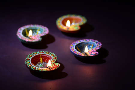Photo for Colorful clay Diya (Lantern) lamps lit during Diwali celebration. Greetings Card Design Indian Hindu Light Festival called Diwali. - Royalty Free Image