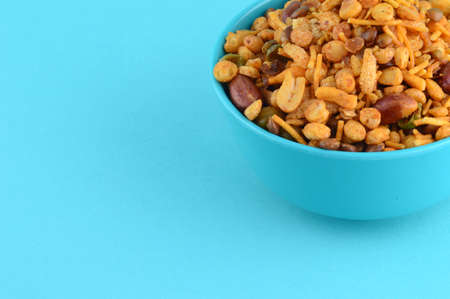 Photo pour Indian Snacks : Mixture (roasted nuts with salt pepper masala, pulses, channa masala dal green peas) in blue bowl in - image libre de droit
