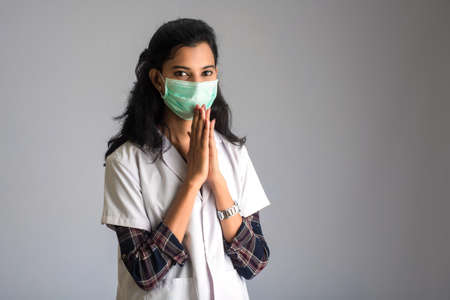 Photo pour Young woman Doctor doing Namaste because of outbreak of COVID-19. New greeting to avoid the spread of coronavirus instead of greeting with a hug or handshake. - image libre de droit