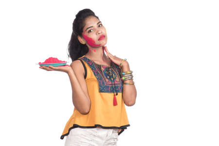 Photo for Beautiful young girl holding powdered color on a plate and enjoying colors on the occasion of the Holi festival. - Royalty Free Image