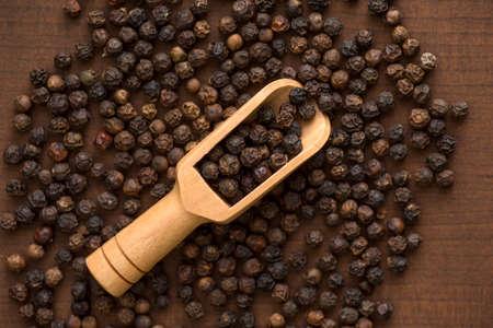 Foto für Close up of black pepper or peppercorns in wood scoop on a wooden background. - Lizenzfreies Bild