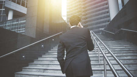 A back of young man dressed in black suit standing on the stairs, watching the sunlight. A young businessman having a call turned his back on the camera